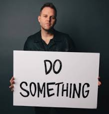 "Matthew West holds ""Do Something"" sign, the song title which inspired Alyssa"